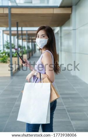 Woman wearing a face mask shopping at department store. Woman wearing a face mask and holding shopping bag walking alone at shopping mall