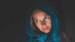 Woman wearing a head scarf looking forlorn.