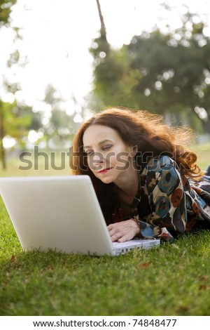 Woman, wearing a hearing aid, working on her laptop in a park.
