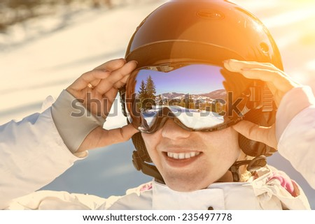 Woman wearing a helmet and glasses on the background of snow winter and mounts.  #235497778