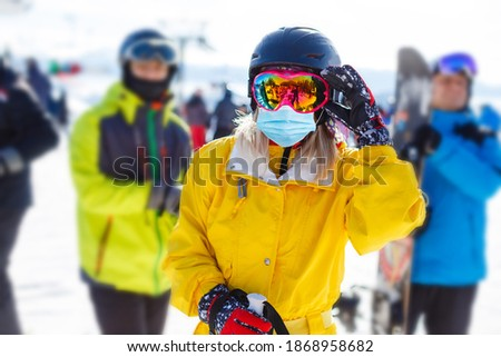 Woman wearing a medical mask during COVID-19 coronavirus on a sunny winter day at a ski resort Stock fotó ©
