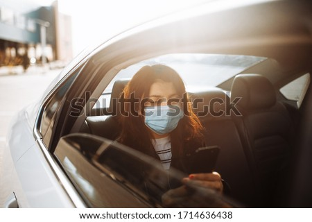 Woman wearing a medical sterile mask in taxi car on a backseat looking out of window checking her cell phone. Girl passenger waiting in a traffic jam during coronavirus quarantine. Healthcare concept Stockfoto ©