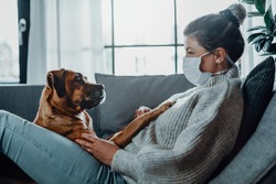 Woman wearing a protective mask cuddles, plays with her dog at home because of the corona virus pandemic covid-19