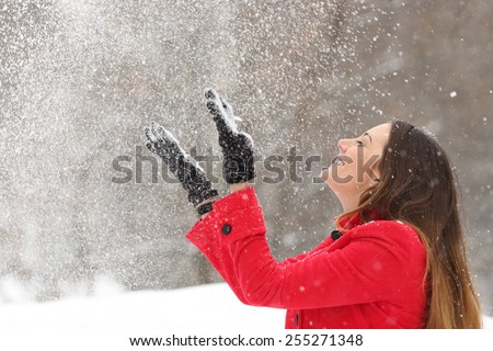 Woman wearing a red jacket throwing snow in the air in winter holidays #255271348