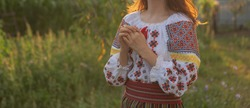 woman wearing a traditional embroidered blouse in sunrise