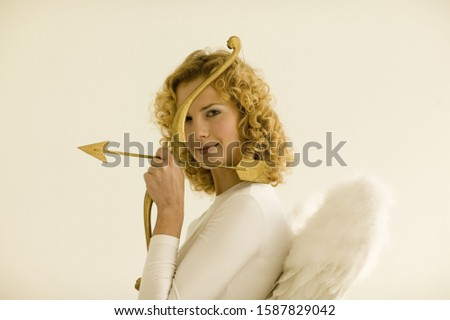 Woman wearing angel wings and holding cupid's bow and arrow