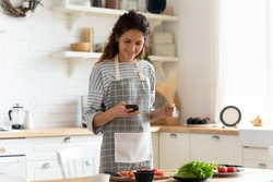 Woman wearing apron standing on domestic kitchen table full of fresh vegetables, housewife holds phone using cooking apps websites search recipes, chatting with friend distracted from food preparation