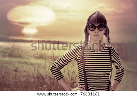 woman wearing aviator hat posing front of nuclear explosion