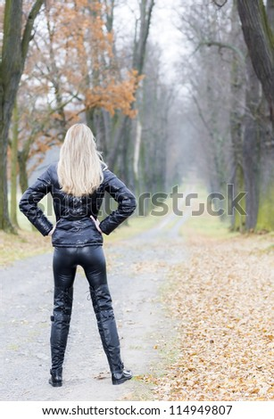 woman wearing black clothes and boots in autumnal alley