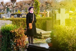 Woman wearing black clothes in cemetery at tombstones graveyard and light flare coming from the cross