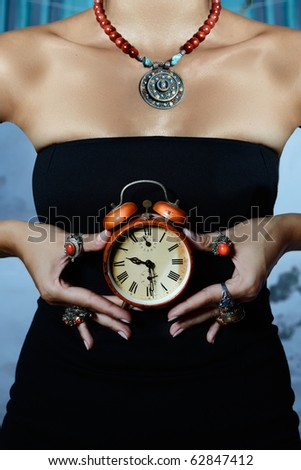 woman wearing black dress and many coral rings holds a red vintage alarm clock