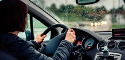 Woman wearing black jacket driving car on the motorway in the rain