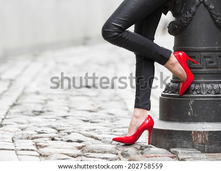 Woman wearing black leather pants and red high heel shoes in old town