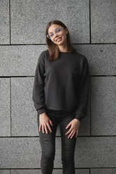 Woman wearing black sweatshirt or hoodie for mock up, logo designs or design prints with with free space on the city streets.