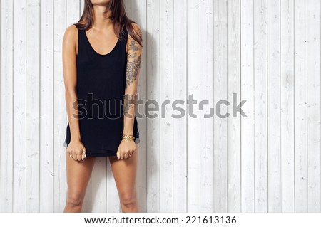 Woman wearing black vest. Wood wall background.