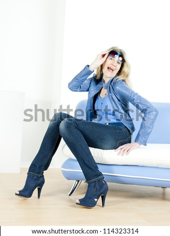 woman wearing blue clothes sitting on sofa - stock photo