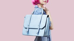 Woman wearing blue dress and pink wig holding big pastel plue messenger bag over white background