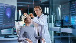 Woman Wearing Brainwave Scanning Headset Sits in a Chair while Scientist Adjusts the Device, Looks at Displays. In the Modern Brain Study Laboratory Monitors Show EEG Reading and Brain Model.