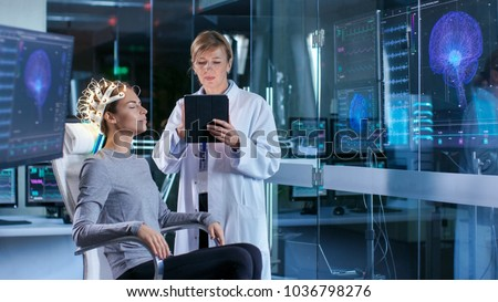 Woman Wearing Brainwave Scanning Headset Sits in a Chair while Scientist Adjusts the Device, Uses Tablet Computer. In the Modern Brain Study Laboratory Monitors Show EEG Reading and Brain Model.