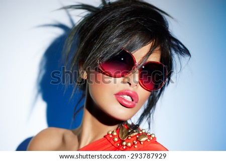 Woman wearing bright red sunglasses, lipstick and dress.