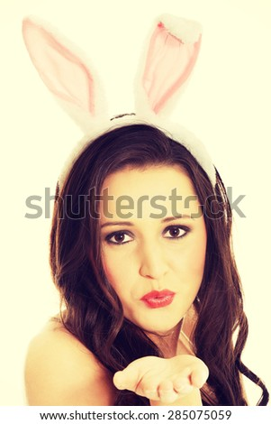 Woman wearing bunny ears and blowing a kiss.