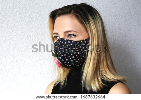 Woman wearing cloth cotton face mask decorated with flowers. Stylish handmade cotton mask. Designed reusable face mask.