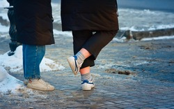 Woman wearing cold shoes on city street in winter, female getting cold feet. Legs with bare ankles, feet dressed in summer sneakers freeze up in cold. Cold weather walk