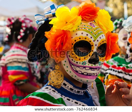 Woman wearing colorful skull mask and paper flowers for Dia de Los Muertos/Day of the Dead