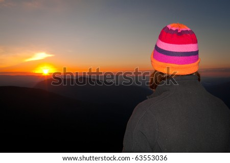 Woman wearing colourful beanie watches sunrise from atop a high mountain