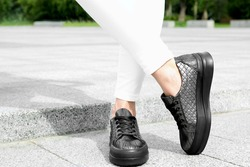 Woman wearing comfortable stylish shoes outdoors, closeup