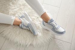 Woman wearing comfortable stylish sneakers indoors, closeup