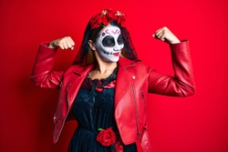 Woman wearing day of the dead costume over red showing arms muscles smiling proud. fitness concept.