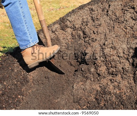 woman wearing denims and workbooks,digging in a pile of topsoil. image shows foot and part of leg.