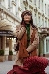 Woman wearing elegant autumn, winter outfit posing in street of European city. Model dressed trendy beige coat, beret, brown scarf, pleated skirt, green turtleneck, with stylish shoulder bag