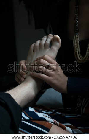 Woman wearing ethno style jewellery and  massaging a man's aesthetic foot.