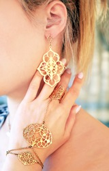 woman wearing expensive gold jewelry - golden bracelet ring and earings