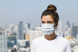 Woman wearing face mask because of Air pollution or virus epidemic in the city