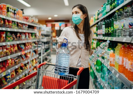 Woman wearing face mask buying bottled water in supermarket/drugstore with sold-out supplies.Prepper buying bulk supplies due to Covid-19 or Coronavirus and panic buying concept.