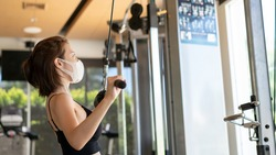 Woman wearing face mask exercising and flexing muscles on lat pull-down cable machine in gym. during corona virus pandermic.