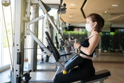 Woman wearing face mask seated cable row, pulling cable of rowing machine training in gym. during corona virus pandermic.
