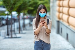 Woman wearing face mask while text messaging on mobile phone at city street. Woman outdoors wearing a facemask while texting on her cell phone.