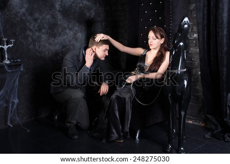 Woman Wearing Formal Black Dress Sitting on Throne with Man Kneeling and Dog Statue Beside Her