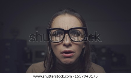 Woman wearing glasses and staring at the computer screen, she has eyesight problems