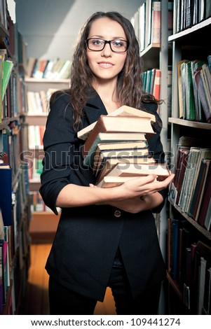 woman wearing glasses holding a pile of books