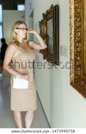 Woman wearing glasses visiting exposition of museum with exhibits of painting