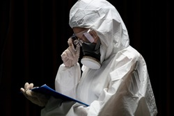 Woman wearing gloves with biohazard chemical protective suit and mask. is writing report on paper.