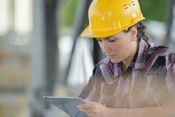 Woman wearing hardhat looking at tablet