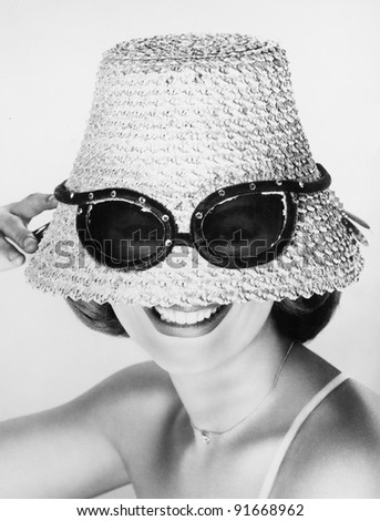 Woman wearing hat with fake sunglasses - stock photo