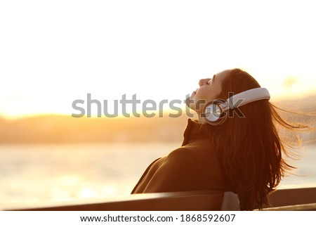 Woman wearing headphones listening to music breathing fresh air relaxing sitting on a bench in winter on the beach