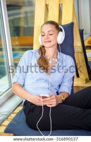 Woman wearing headphones listening to music on your phone. Feel relaxed with the help of music. Young beautiful girl listening to music on headphones during a work break. Woman student. Life style.